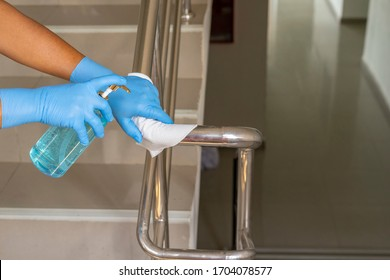 Staff disinfecting stainless streel staircase railing by spraying disinfectant from the bottle on wet wipe.Antiseptic,disinfection,cleanliness and healthcare. Anti bacterial and Corona virus COVID-19.