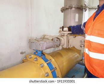 The staff dressed in an orange warning vest check the knife valve in wastewater pipe. Man does duties