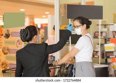 Le personnel de l'épicerie avec thermomètre vérifiant la température du client pour la protection Coronavirus.