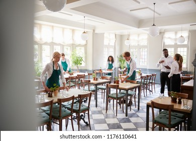 Staff Laying Tables In Empty Restaurant
