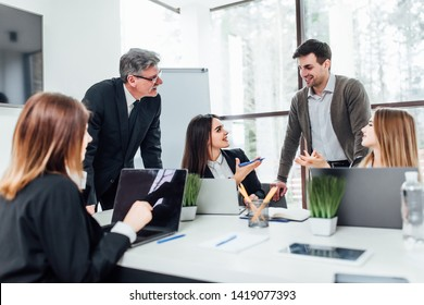 Staff meeting. Group of  five young modern people in smart casual wear discussing something while working in the creative office .