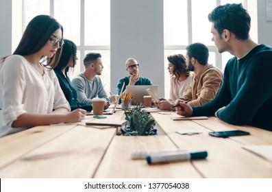 Réunion du personnel. Groupe de jeunes gens modernes en tenue décontractée intelligente discutant de quelque chose en travaillant dans un bureau de création