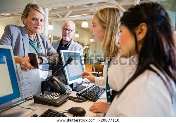 Staff Talking With Businesswoman At Airport Check-in
