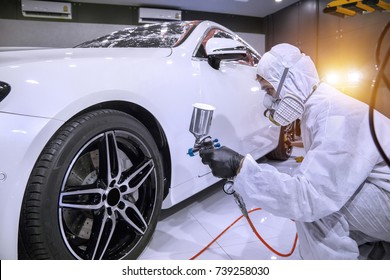 Staff wear Chemical protective clothing at work.Car Care Business. Automobile industry. Car wash and coating business with ceramic coating.Spraying the varnish to the car.