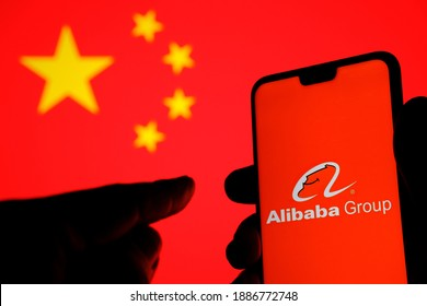 Stafford, UK - January 3 2021: Alibaba logo on a silhouette of smartphone and hand pointing at it. Blurred China flag on the background laptop. NO EDIT IN POST, NO ALTERATION, REAL PHOTO.