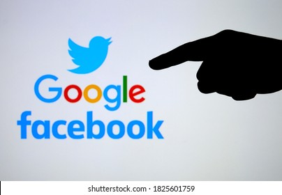 Stafford  UK - October 1 2020: Silhouette of hand pointing Twitter, Google, Facebook logos on the blurred screen. Concept for  Big Tech court case.