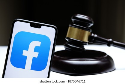 Stafford, United Kingdom - December 15 2020: Facebook logo seen on the smartphone placed next to the judges gavel. Concept for a lawsuit, legal case, antitrust and fine. Real photo, not a montage.