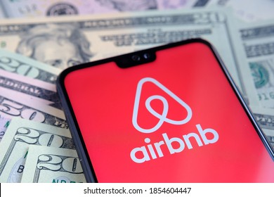 Stafford, United Kingdom - November 15 2020: Airbnb app logo seen on the screen of smartphone, placed on dollar bills. Concept for IPO and company profit.