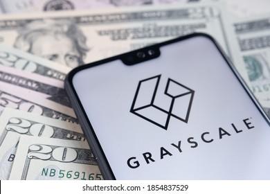 Stafford  United Kingdom - November 15 2020: Grayscale Bitcoin Trust company logo seen on the screen of smartphone, placed on dollar bills.
