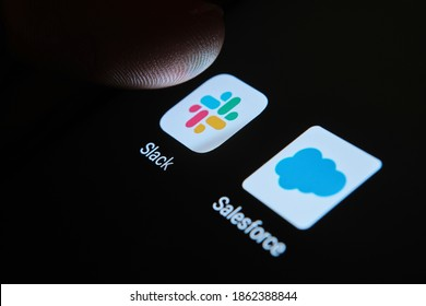 Stafford, United Kingdom - November 26 2020: finfertip on top of Slack and Salesforce apps on the smartphone screen. Concept photo for merger deal. SELECTIVE FOCUS.