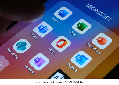 Stafford / United Kingdom - September 29 2020: Microsoft Office 365 products as mobile apps seen on the screen of smartphone and blurred finger pointing at it.