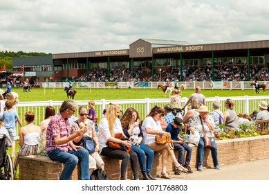 Staffordshire, England - June 01,2017 : Group of people sitting relaxed enjoying ice cream cones watching equestrian activities on a warm sunny day at the  Staffordshire County Show
