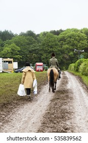 Staffordshire, England - May 29th 2014  : Young female equestrian riding her horse down muddy country lane towards horsebox with older female on foot walking with carrier bags  Staffordshire, England.