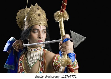 Stage artist dressed-up as Rama and holding a bow and arrow