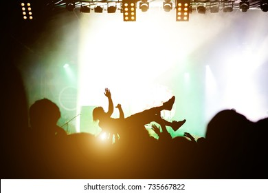 Stage diving. Crowd surfing during a musical performance. Silhouette of man.