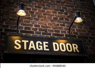 Stage door at London theatre illuminated by spotlights