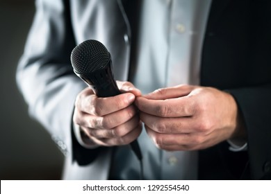 Stage fright concept. Nervous and shy public speaker with microphone. Business man afraid of giving speech for crowd of people or audience. Sweaty hands holding mic. Bad presentation. Stressed singer.