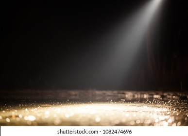 Stage light and golden glitter lights on floor.