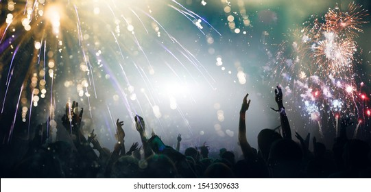 Stage lights and crowd of audience with hands raised at a music festival. Fans enjoying the party vibes. New Years Eve concept.
