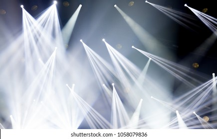 Stage lights on concert. Lighting equipment with white colored beams.