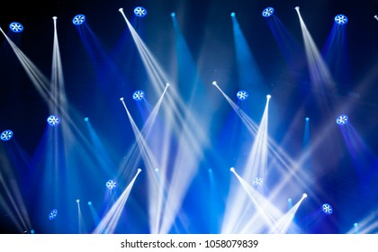 Stage lights on concert. Lighting equipment with blue colored beams.