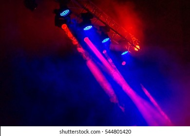 Stage lights. Several projectors in the dark. Multi-colored light beams from the stage spotlights on the stage in the smoke at the time of the entertainment show. Night club