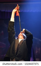 A stage magician takes the centre spotlight during his sword swallowing act