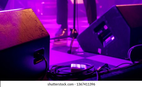Stage monitor speakers and cables in purple ambient light at band live gig