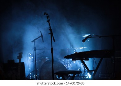 A stage set with instruments and microphones. The smoke and blue light that shows the silhouet of the mics gives a groovy vibe. A typical stage scene. Concept of concerts, shows, stage music and bands