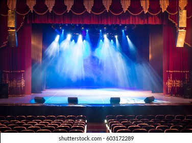 The stage of the theater illuminated by spotlights from the auditorium