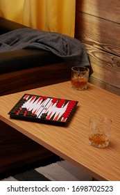 Staged photo of backgammon on the bedside table with whiskey glasses near the couch and a yellow curtain. The narde set consists of a folding board, black and red playing chips and two cubes.