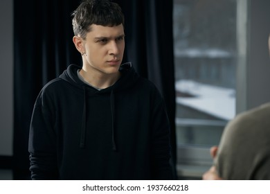 Staged photo illustrates problems and conflicts in gay couple relationships. Moment of showdown: young black-haired man with furrowed brow is looking at his partner.