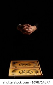 Staged photo of male hands with interlocked fingers over a backgammon in the darkness. The narde set consists of a wooden folding board, dark and light playing chips and two cubes.