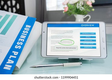 Stages of writing a business plan to meet business goals, printed document with pen and making edits on tablet or mobile device.