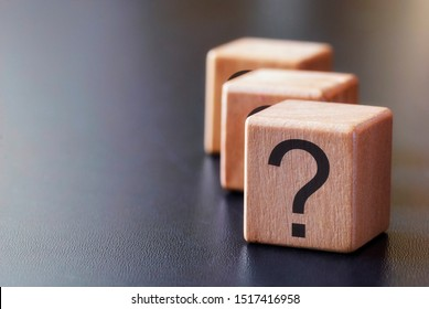 Staggered row of three wooden blocks with question marks forming a side border over grey with copy space