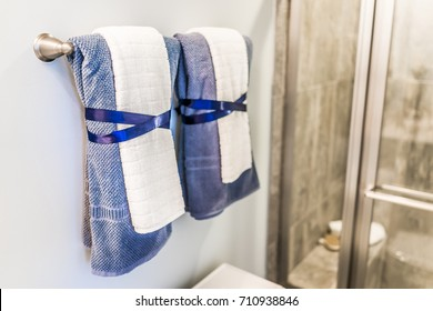Staging modern bathroom with two decorated towels hanging on rack by shower in model home, apartment or house