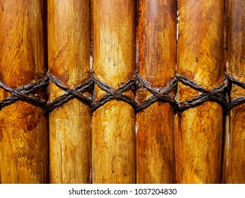 A stained bamboo fence and the rope lashing it together.