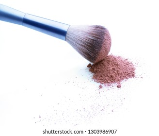 Stained brush over pile of makeup powder. White background. Copy space against powder remnants.