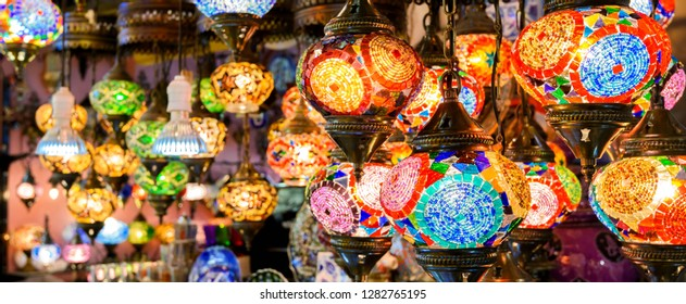 Stained glass lamps in Grand Bazaar, Istanbul, Turkey. Panoramic view of colorful oriental gifts. Beautiful lamps in artisan market close-up. Arab and Turkish craft products in eastern bazaar.