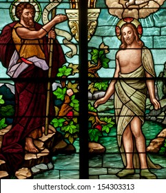 Stained glass window depicting Bible story of Saint John the Baptist baptizing Jesus in the Jordan River