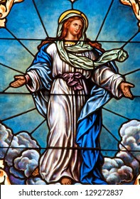Stained glass window depicting Catholic devotion of Assumption of Blessed Virgin Mary into Heaven