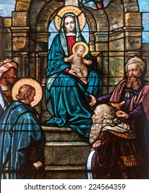 Stained glass window depicting Christmas scene of the adoration of the magi with Mary holding the child Jesus
