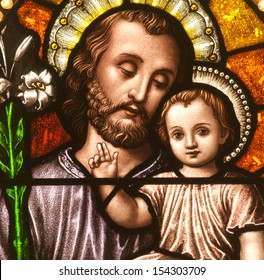 Stained glass window depicting closeup of Saint Joseph with the child Jesus