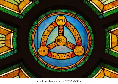 Stained glass window depicting doctrine of the Holy Trinity in Latin with symbols of circle and triangle