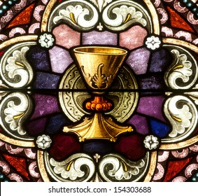 Stained glass window depicting a golden chalice and paten