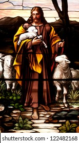 Stained glass window depicting Jesus Christ as the Good Shepherd with sheep