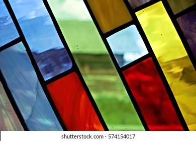 Stained glass window looking out onto a barn.