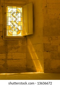 Stained Glass window with rays of golden light on stone wall