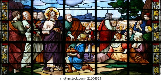 Stained glass window in St.Sulpice church (Fougeres, France), depicting a biblical scene:miracle of Jesus Christ by feeding a crowd of 5.000 with just five loaves of bread and two small fish.