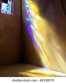 Stained Glass window with sun rays of colored light on wall and floor. St. Giles Cathedral. Edinburgh. Scotland. UK.